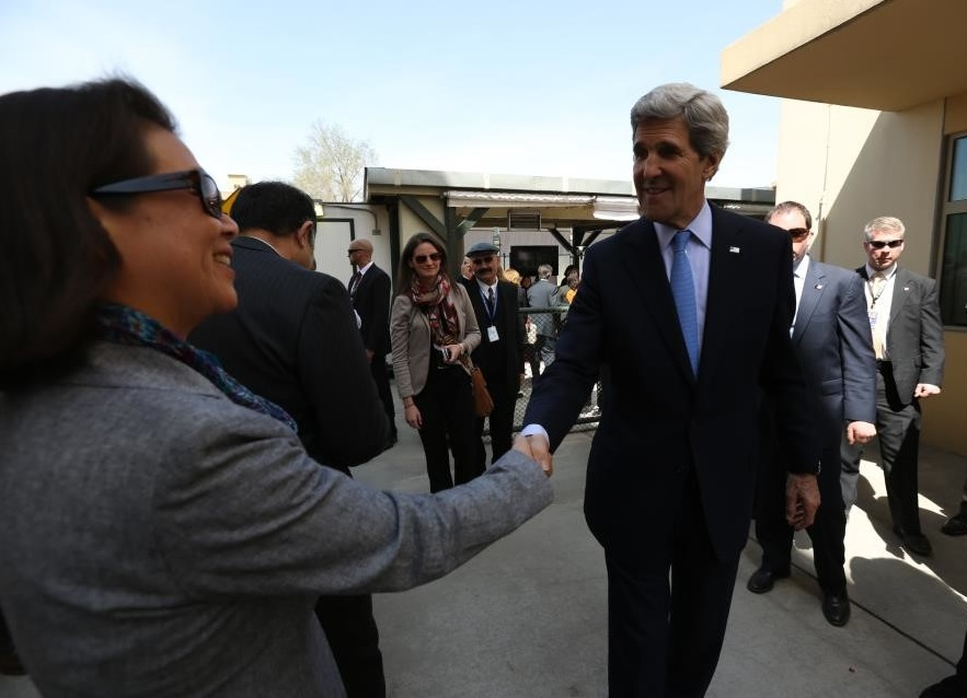 Former U.S. Secretary of State John Kerry reaches out to shake the hand of a man shortly after arriving in Kabul, Afghanistan, in 2013.