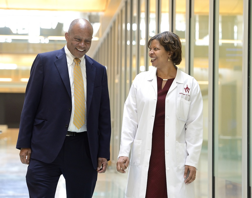 A man wearing a suit and a woman wearing a white lab coat walk down a light-filled corridor, deep in conversation.