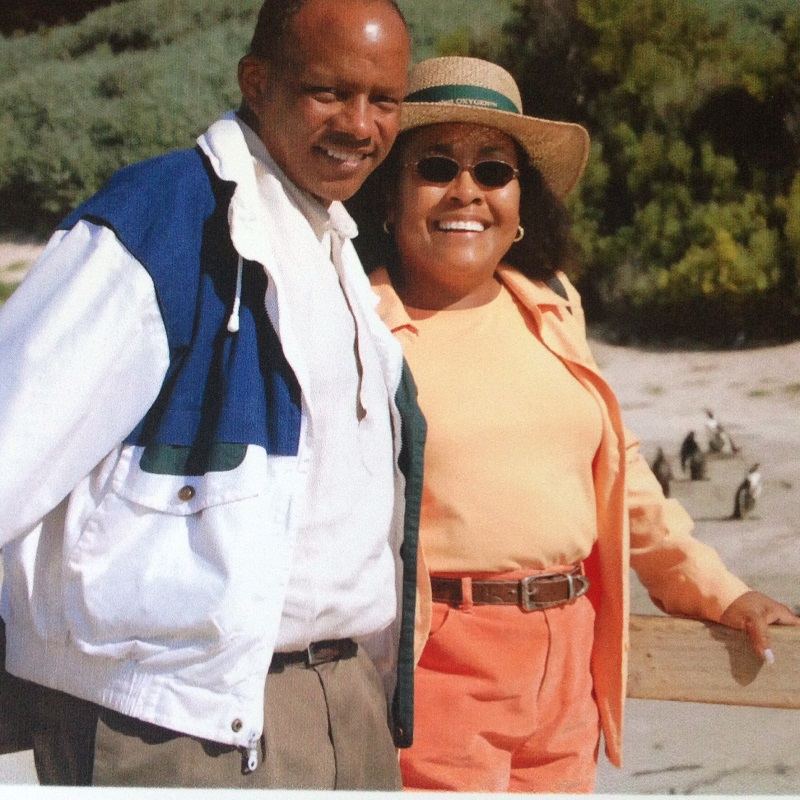 A man and woman in leisure attire pose for a photo on a secluded beach during their vacation.