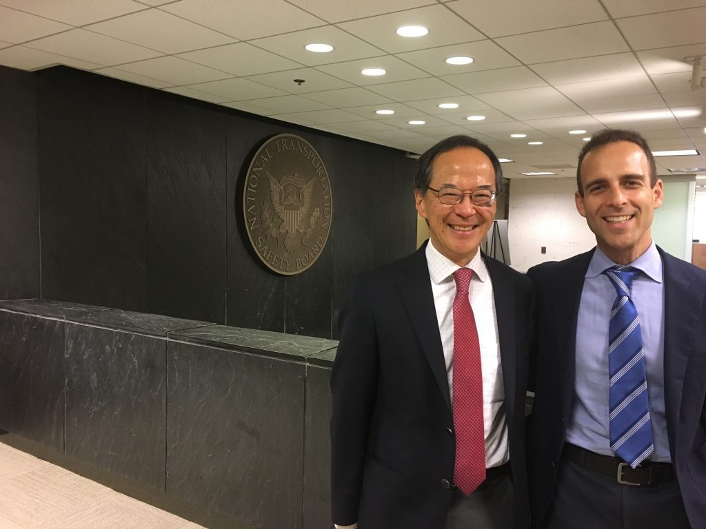 Researchers Tak Igusa and Johnathon Ehsani pose for a portrait in front of the seal of the National Transportation Safety Board.