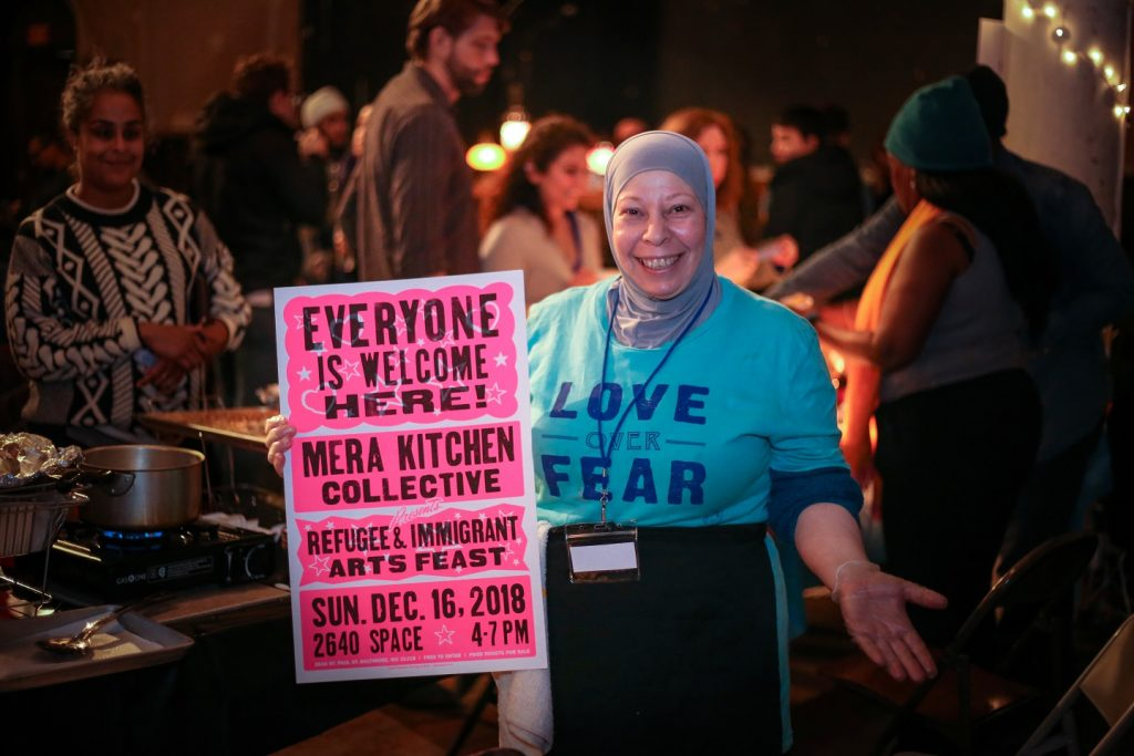 """A woman stands in front of a portable stove holding a brightly colored sign reading """"Everyone is welcome here!"""" during a refugee and immigrant arts feast."""