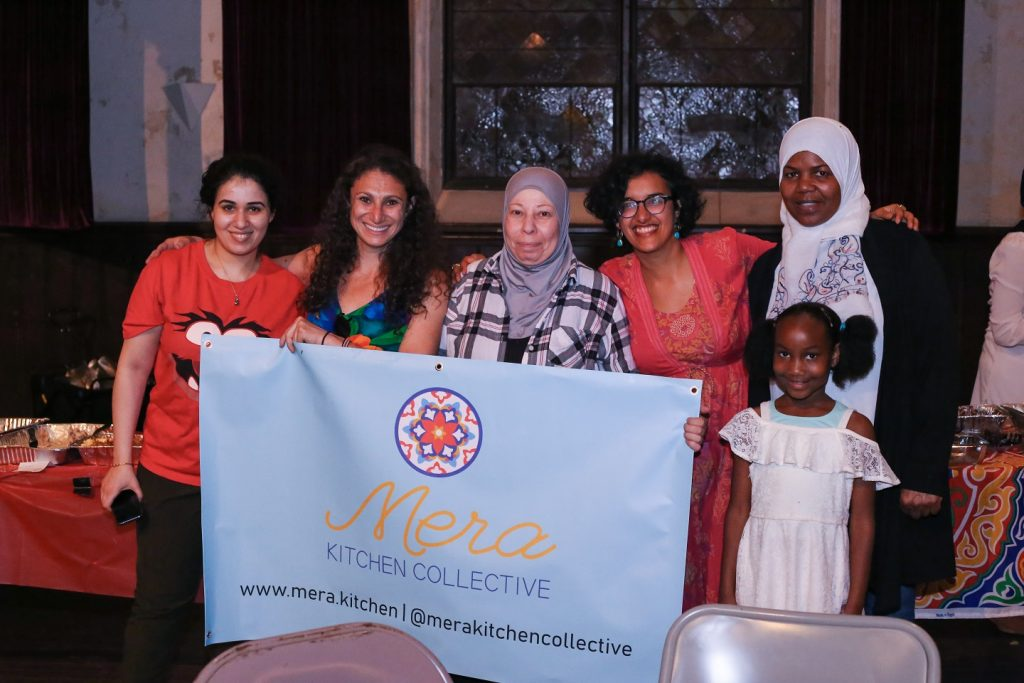"""Five women and a young girl stand in front of a table holding a sign that says """"Mera Kitchen Collective"""" during one of the collective's events."""