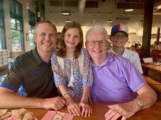 An older man with white hair and wearing glasses and a purple shirt sits a table in a naturally lit restaurant with a younger man in a green polo shirt, a girl approximately nine years old in a blue patterned dress, and a boy approximately seven years old wearing a with white shirt and a baseball hat.