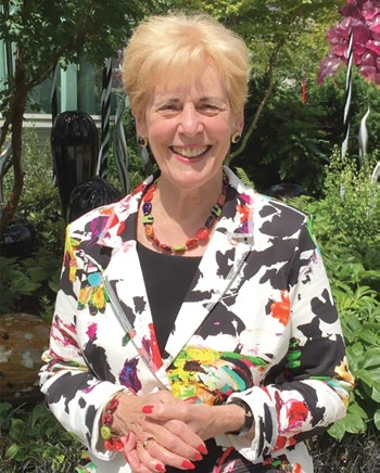 Jill McGovern smiles at the camera in a black and white suit with splashes of color with a green garden in the background