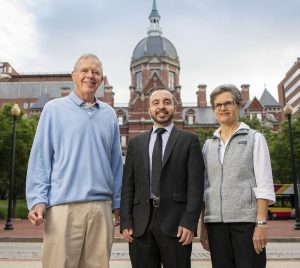 Two men and one woman stand in front of the dome of the old Johns Hopkins Hospital building on a sunny day