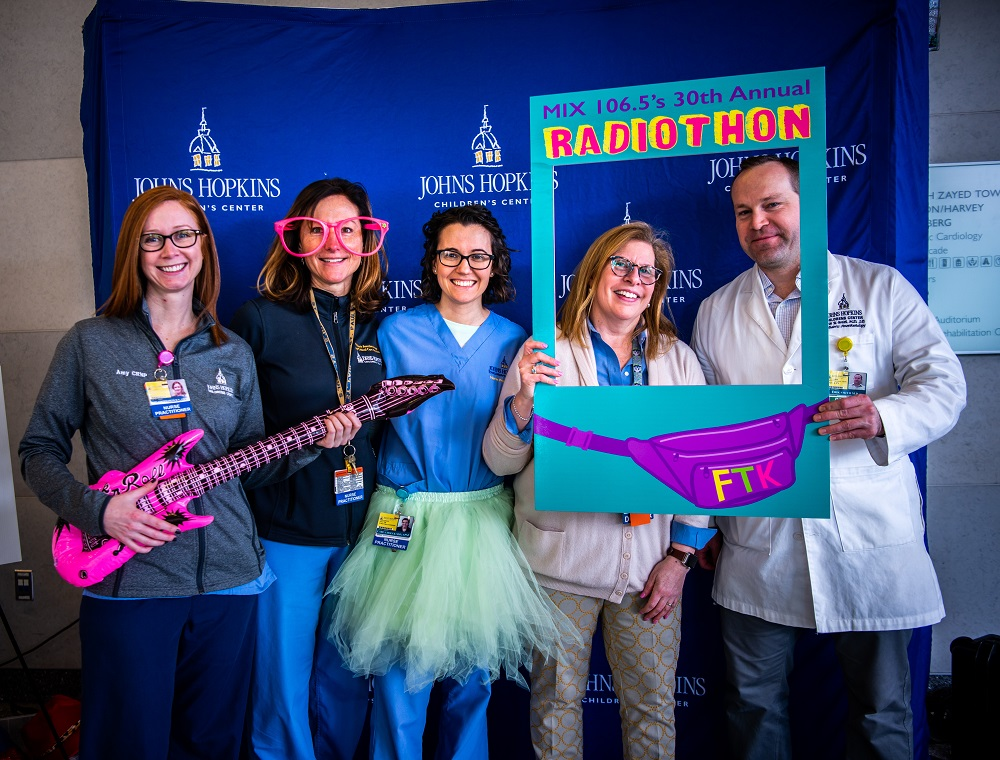 Four woman and a man wear costumes and hold props in front of a blue Johns Hopkins Children's Center backdrop during the Radiothon.