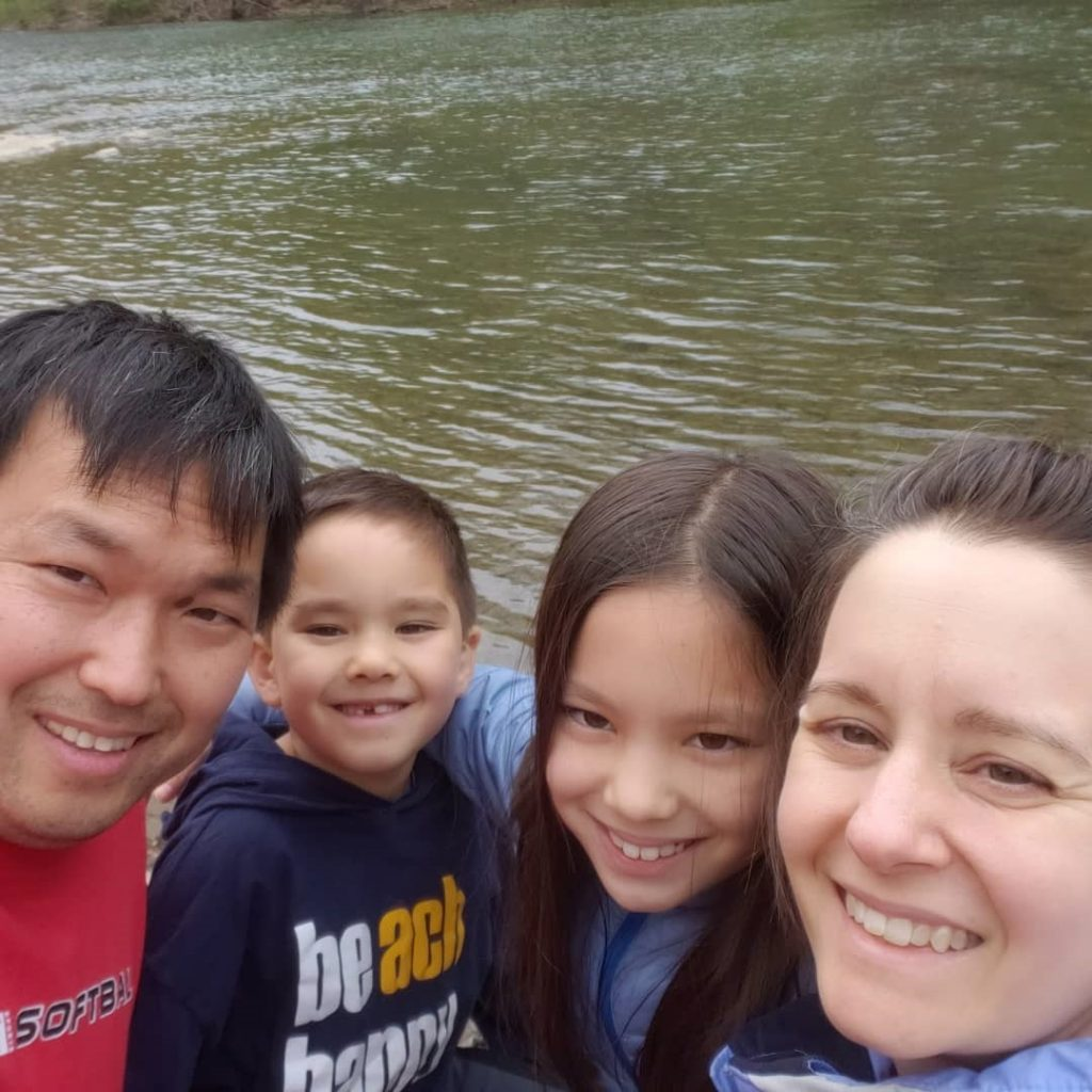 A selfie photo of John, Evan, Zoe, and Lindsey Kim standing near the side of a pond.