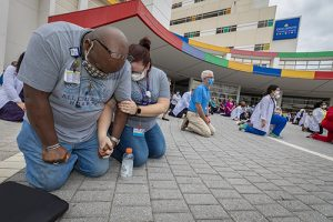 A man and a woman kneel beside several other people, also kneeling, on the sidewalk outside Johns Hopkins All Children's Hospital in Tampa, Florida.