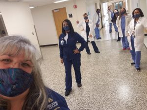 Several members of a surgery unit line the walls of a hospital hallway to take a group selfie.