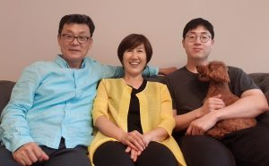 Three people - Jacob Lee, Nohee Kwak, and their son Brian - sit on a couch. Brian holds the family dog, Choco, on his lap.