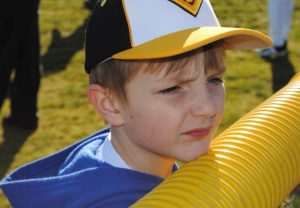 A young boy wearing a black, yellow, and white baseball cap stands on the sideline of a baseball field, resting his chin on the top of a fence.