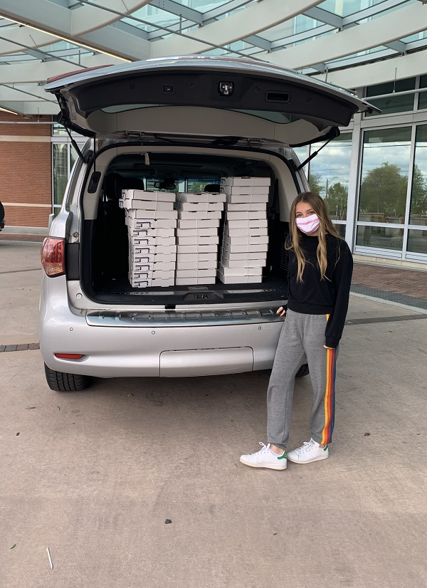 A young woman wearing a face mask stands at the rear of a minivan. The van's back gate is open and inside the back are dozens of pizza boxes.
