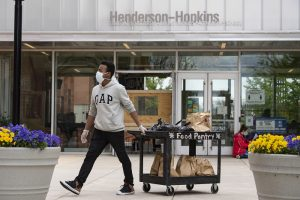 A man wearing a mask and plastic gloves pulls a black cart laden with bags of groceries past the entrance of the Henderson Hopkins School.