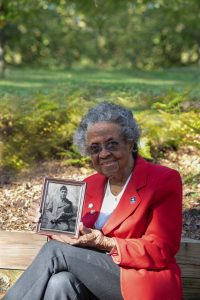 Mille Bailey sits on a bench holding a framed photo of her husband.