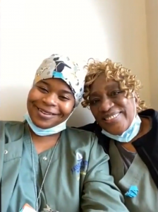 Two nurse technicians pictured from the waist up and wearing green scrubs and face masks pulled down to their chins. The one on the left has on a white headscarf covering her hair and the one on the right has curly hair.