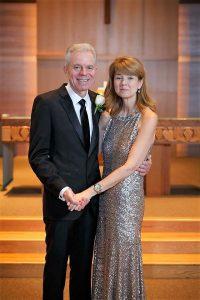 Derrick-Kuzak-wearing-suit-holding-hands-with-Kate-Kuzak-in-silver-dress