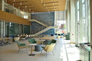 A bright and open space inside a building with lots of vertical windows, open staircase, green and yellow chairs, and long tables.