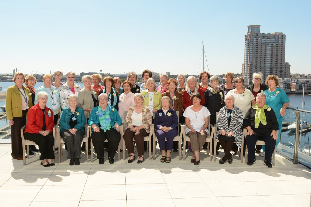 A group photo featuring more than 30 women standing and sitting on a terrace with water and a tall building in the background.