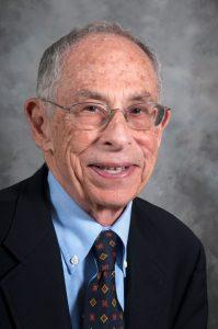 Portrait of Allen Root wearing eye glasses a dark blue blazer, light blue shirt and dark blue tie