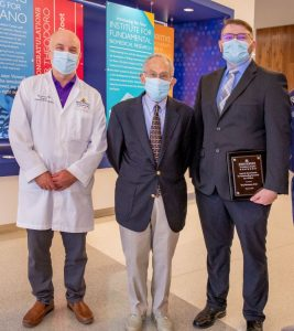 Three men, all with face masks, stand for a photo. The man on the left wears a white medical coat over a purple shirt and gray pants. The man in the center wears khaki pants with a dark blue blazer, light blue shirt and dark blue tie. The man on the right wears a dark gray suit with a blue shirt and gray tie.