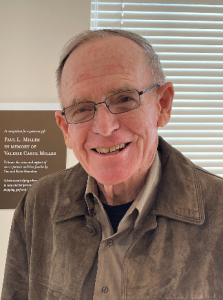 Portrait of Paul Miller wearing a brown jacket, tan shirt, and eye glasses