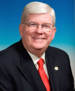 Portrait of George Doetsch wearing a navy pinstripe suit jacket, white shirt, red tie, and eye glasses