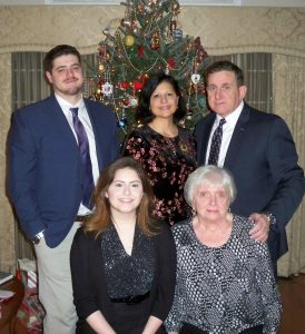 Members of the Rendon-Sherman family in front of a decorated Christmas tree. Sitting are a woman with long brown hear wearing a black top, sweater, and skirt, and a woman with short white hair wearing a black and white top. Standing are a man with short brown hair, tan pants, navy jacket, white shirt, and navy tie; a woman with shoulder-length black hair and a black and pink top; and a man with short brown hair waiting a navy jacket, white shirt, and navy tie.