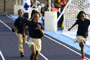 three-children-in-school-uniforms-running-on-track