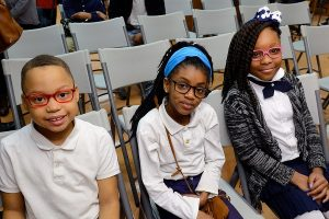 three-students-in-uniforms-sit-similing-and-wearing-glasses